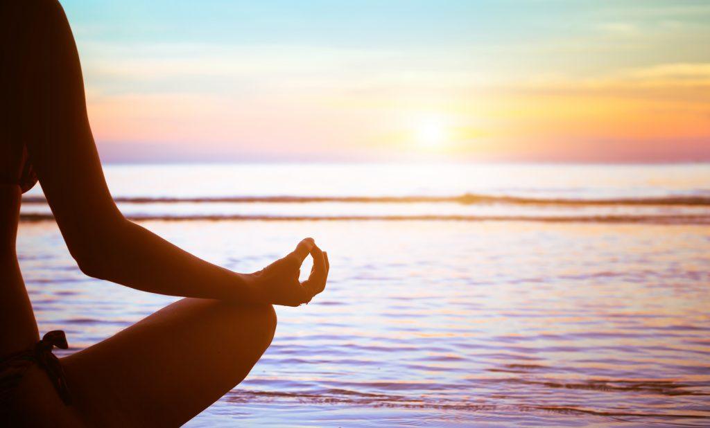 Woman Meditating with sunrise